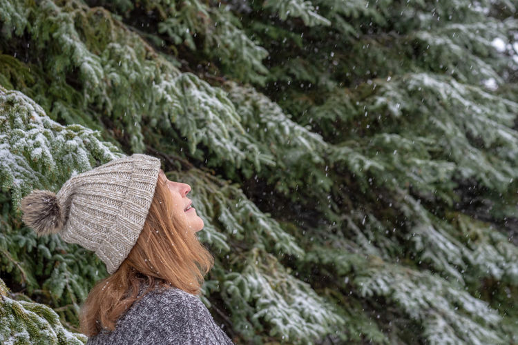 woman looking up at snow falling in pine forest at Christmas One Person Headshot Hat Clothing Adult Women Portrait Plant Leisure Activity Tree Hair Day Lifestyles Nature Real People Forest Long Hair Outdoors Environment Hairstyle WoodLand Snow Snowing Snowflakes Christmas Tree Holiday Season  Copy Space Fall Falling