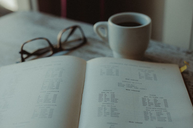 Coffee Coffee Break Coffee Time Studying Reading A Book Book Old Book French Vocabulary Education Learning Eyeglasses  Glasses Close-up No People Indoors  Drink Still Life Paper Cup Mug Publication Table Communication Coffee Cup Text Western Script Food And Drink Coffee - Drink Textbook Open