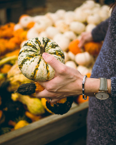 Midsection of woman holding pumpkin at market