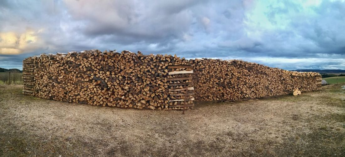 Stacked firewood in dramatic landscape Wood Firewood Stacked Stock Wide View Panorama Material Heat Wooden Oven Landscape Clouds Early Spring Forestry Trees Sky Cloud - Sky Forestry Industry Countryside Fire Pit Woodpile Deforestation Farmland