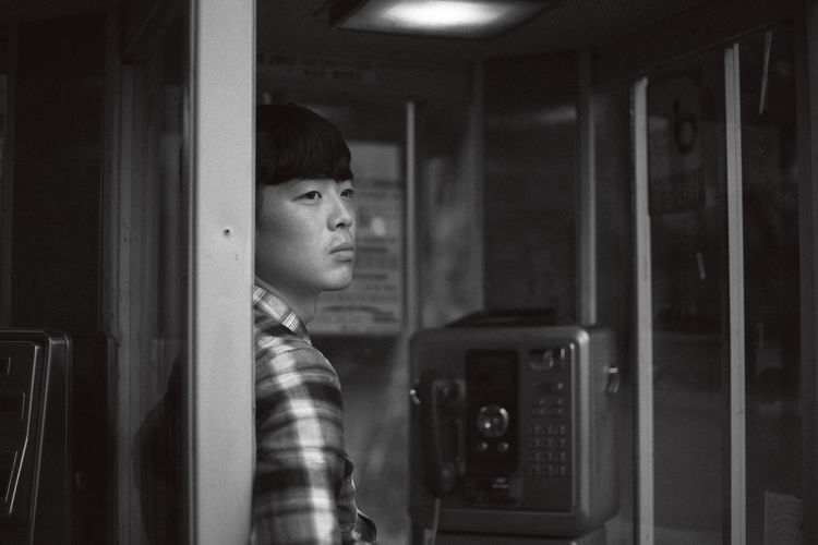Young man at telephone booth