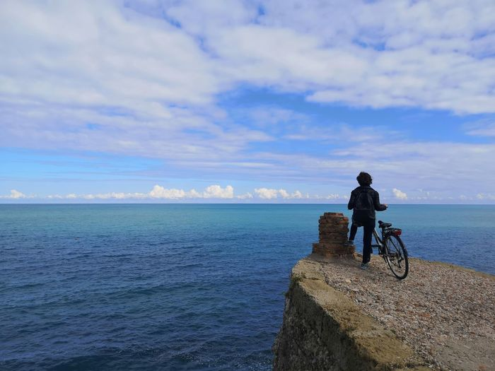 Rear view of man riding bicycle by sea against sky
