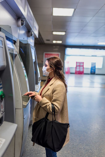 Woman wearing mask using atm at mall