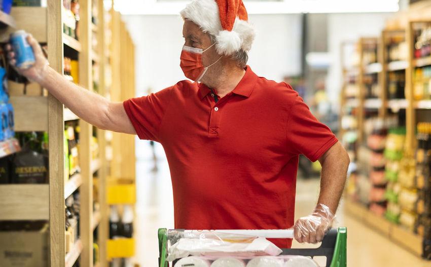 Senior man wearing mask standing at shopping mall