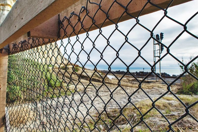 View of the beach through a chainlink fence against sky