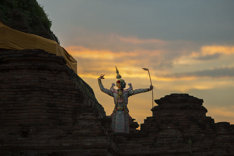 Man wearing traditional costume while standing on temple building against sky during sunset