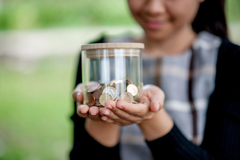 Midsection of woman holding glass jar with coins