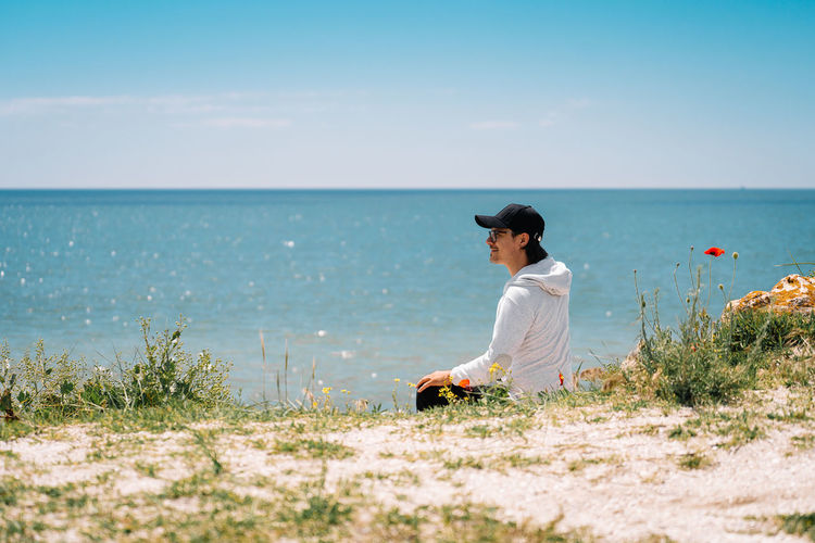 Woman sitting on beach looking at sea against sky