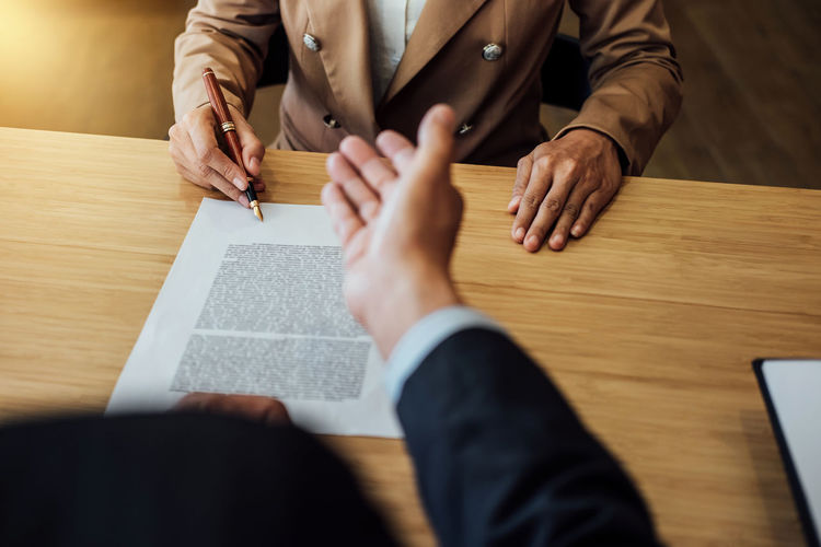 Midsection of businessman signing contract while colleague gesturing on table