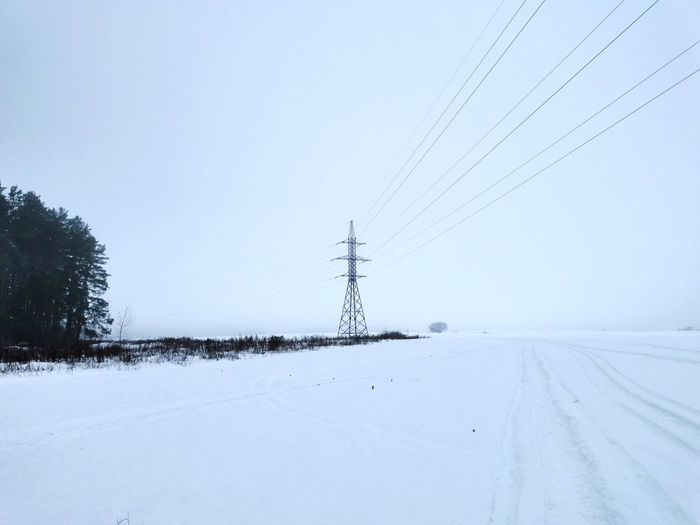 Electricity pylon on snow covered landscape against sky