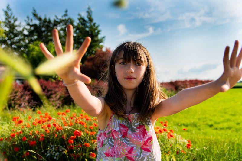 Portrait of happy girl standing on field against sky