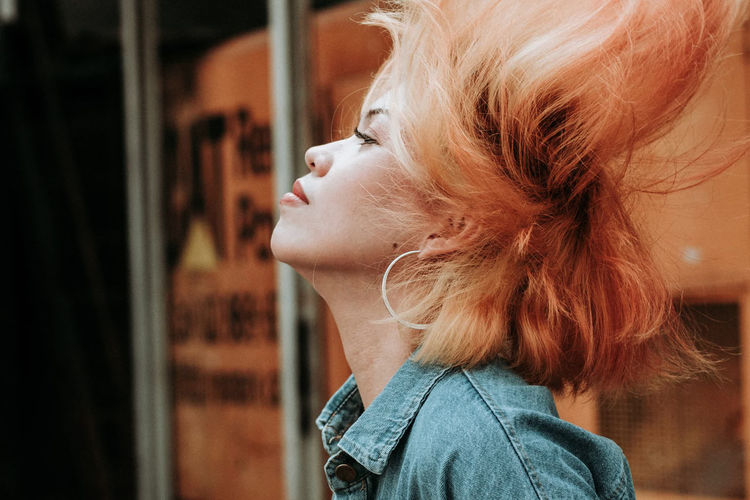 Profile view of woman with tousled hairs outdoors