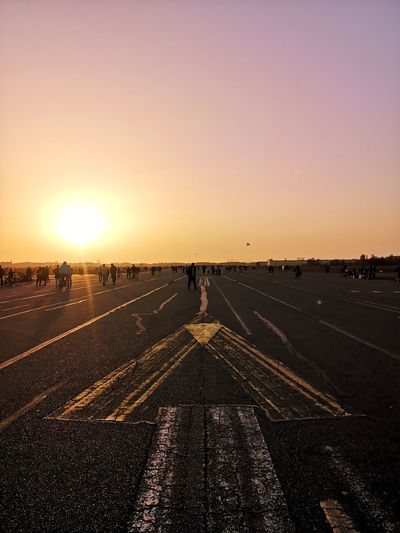 Man walking on road against sky during sunset