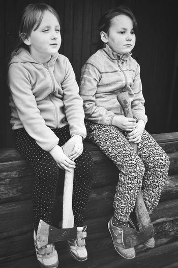 Full length of sisters with axe looking away while sitting on wooden railing