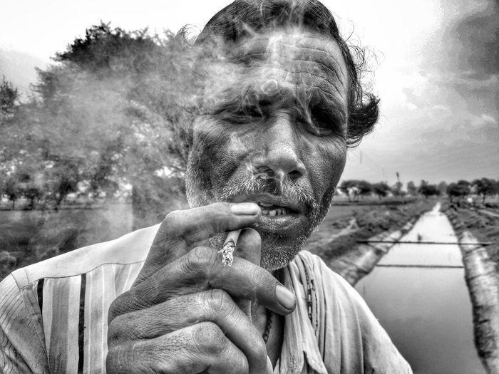 Portrait of man smoking bidi against sky