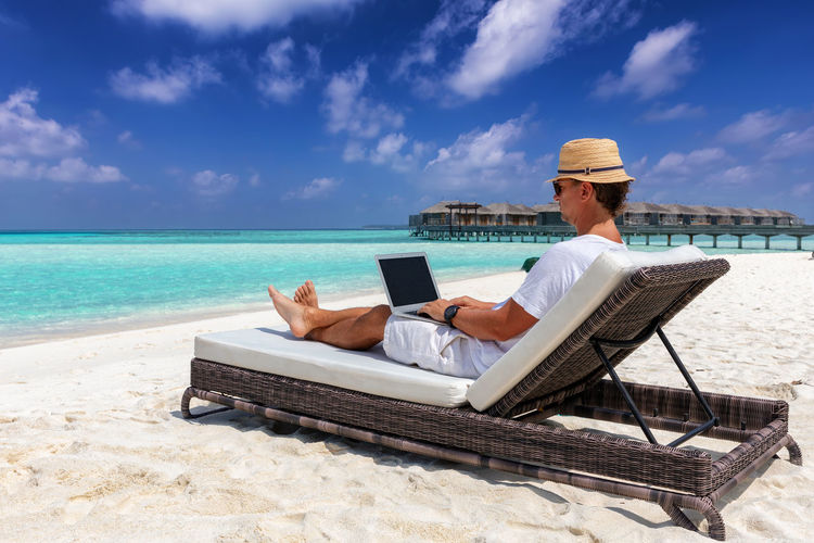Man using laptop while sitting on lounge chair at beach against sky