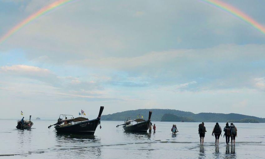 People on sea against sky