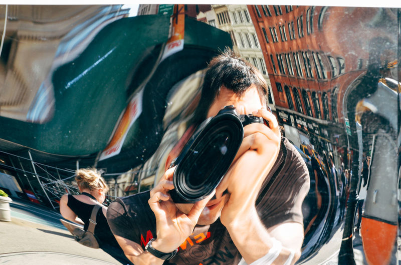 Reflection of man clicking selfie with camera