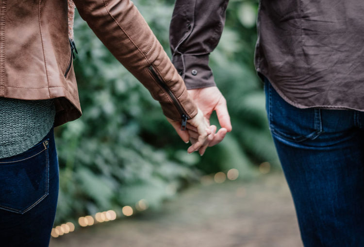 Close-up of holding hands Brown Colors Couple Couples In Love Emotions Holding Hands Intimate Love Moments Romance Romantic Casual Clothing Close-up Couple - Relationship Couplegoals Emotional Moments Focus On Foreground Human Hand Standing Taken From Behind Together Togetherness Two People Walking