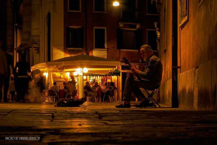 Street musician in Venice Street Streetphotography Street Musician Musician Old Man Venice Venice, Italy Night Glowing Temple - Building Person Sitting