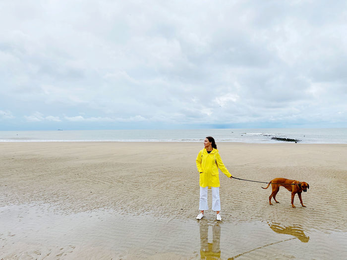 Man standing with dog on beach