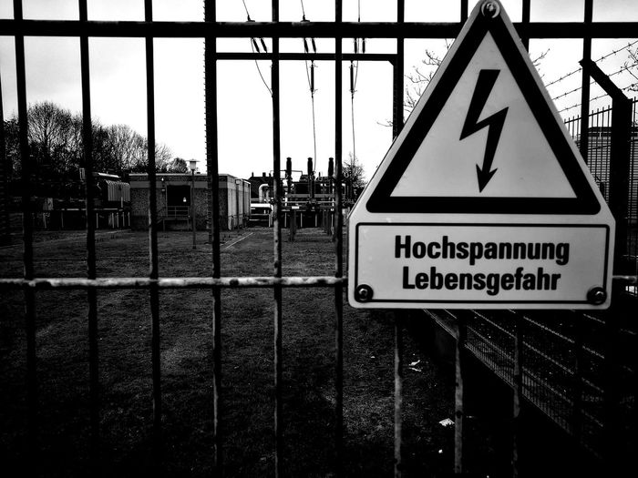 Close-up of warning sign on metal fence