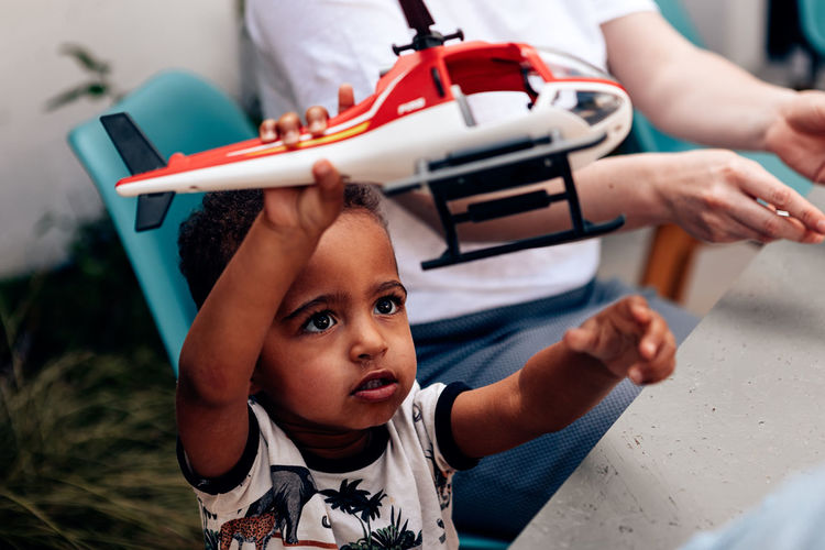 Mixed race little child plays with toy helicopter standing nearby the table where his mum sits