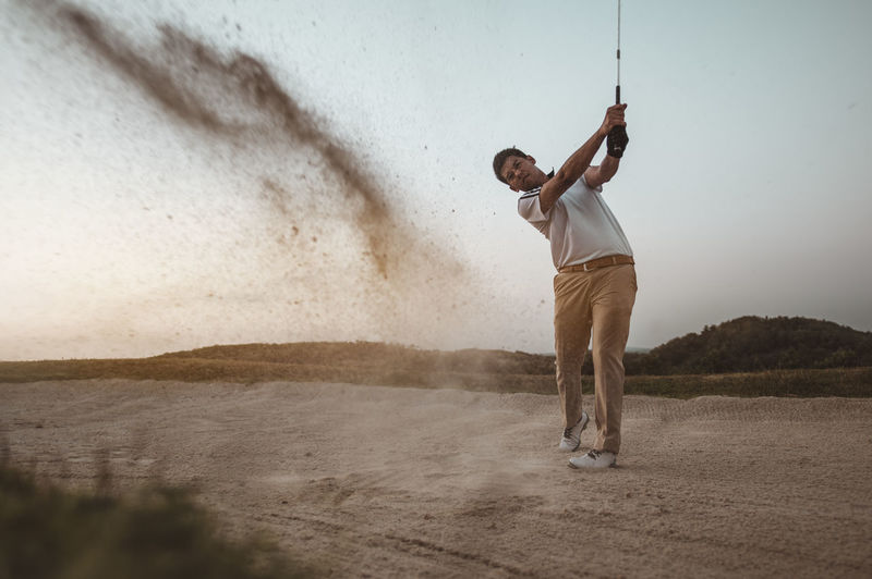 Full length of man playing golf against sky at sunset