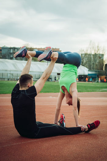 Young Couple Exercising On Sports Track
