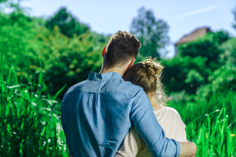 Adult Beauty In Nature Bonding Casual Clothing Couple - Relationship Day Focus On Foreground Friendship Grass Green Color Heterosexual Couple Leisure Activity Lifestyles Love Men Nature Outdoors People Real People Rear View Togetherness Two People Women