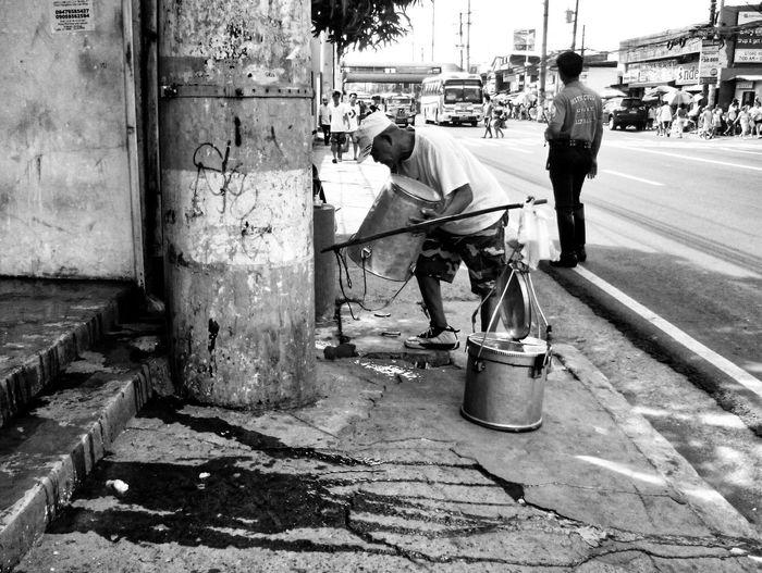 Man Carrying Buckets On Sidewalk