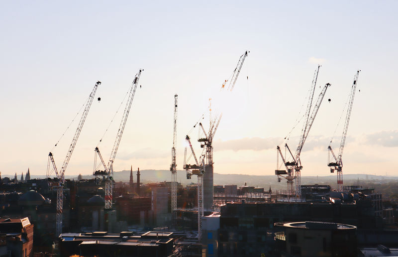 Cranes in city dock against sky