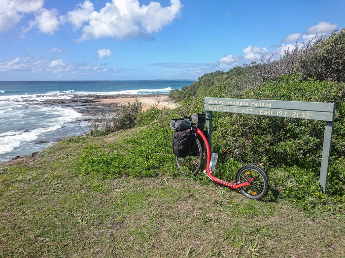 Kickbike leaning on sign overlooking coastal view Beach Bicycle Coastline Day Horizon Over Water Kickbike Outdoors Sand Sea Shore Stationary Transportation