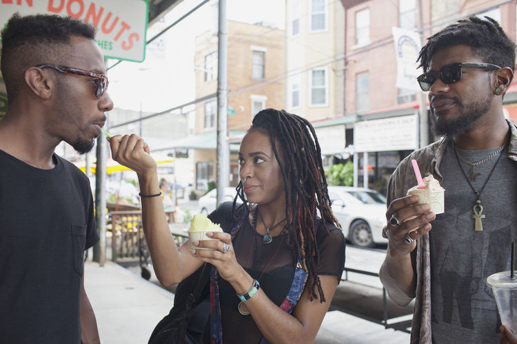 Young man drinking glass with woman standing in city