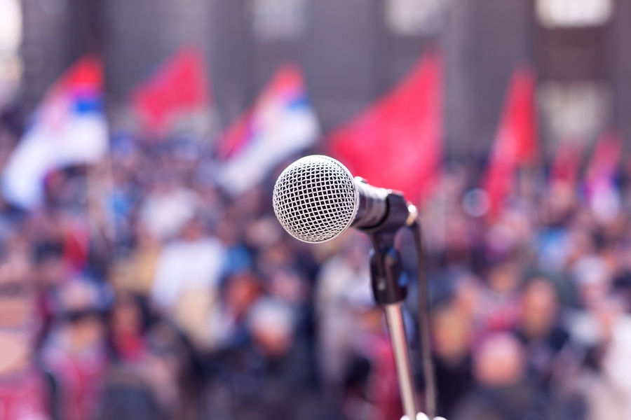 Microphone in focus against blurred crowd Auditorium Civil Resistance Meeting Politics Protest Public Transportation Audience Convention Crowd Elections Flags Group Human Right Justice Labor Mass Microphone Microphones Nonviolent Resistance People Political Rally Protesters Speaker Unrecognizable Unrecognizable Person