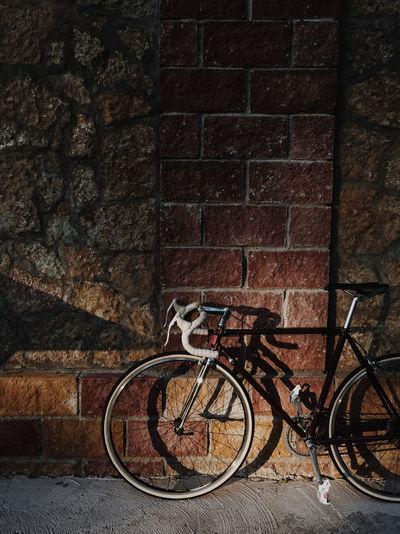 Race bike Activity Bicycle Bike Brick Brick Wall Land Vehicle Leisure Leisure Activity Mode Of Transportation No People Outdoors Outdoors Activity Parking Race Race Bike Sidewalk Stone Wall Transportation Wall Wall - Building Feature