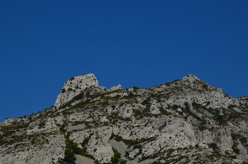 Low angle view of rocky mountain against clear blue sky