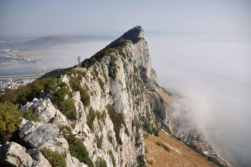 Scenic view of sea by mountain against sky in gibraltar