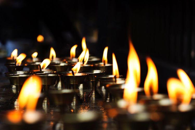 Close-Up Of Burning Diyas In Temple