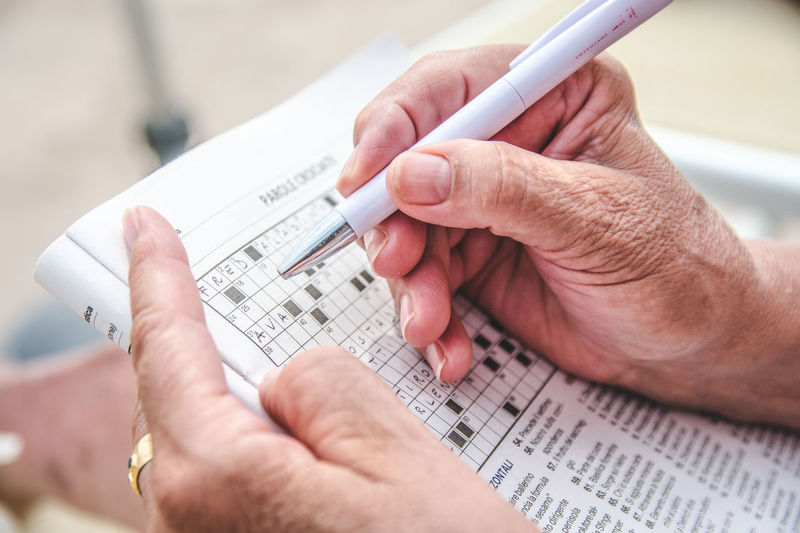 Cropped Hands Solving Puzzle On Newspaper