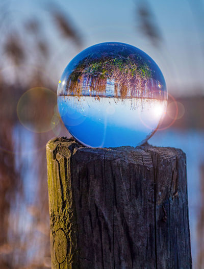 Close-up of crystal ball on wooden post