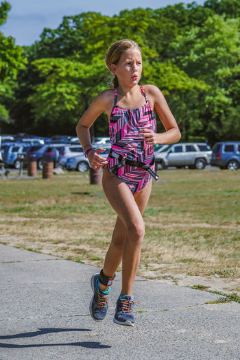 Young girl triathlete competing in race running Athlete Attitude Child Children Only Competing Competition Competitor Determine Full Length Girl Healthy Lifestyle Lifestyles One Girl Only One Person Outdoors People Race Running Shorts Sport TRIATHLON Winning