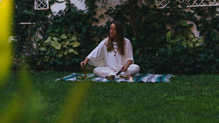 Full length of young woman making herbal medicine while sitting outdoors