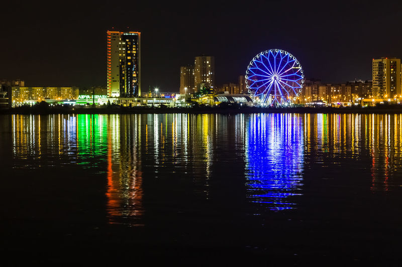 Illuminated ferris wheel by river against buildings at night