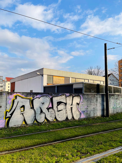 Graffiti on wall by railroad tracks against sky