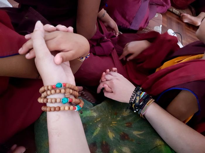 Series: Never Ending Peace And Love || Title: friendship 1 Children Togetherness Hand Holding Hands Nepal Kathmandu Buddhism Buddhist Nun Nunnery Warmth Friendship Multi Cultural Red Orange Color Human Hand Togetherness Low Section Women Celebration Close-up Holi