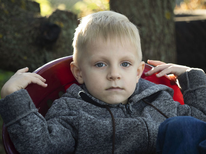 Little caucasian boy sitting in armchair in the garden Little Caucasian Sitting Armchair Garden Plastic Outdoors Portrait Child Childhood Looking At Camera Boys Men One Person Males  Real People Innocence Cute Headshot Day Lifestyles Front View Warm Clothing Blond Hair Baby Hair