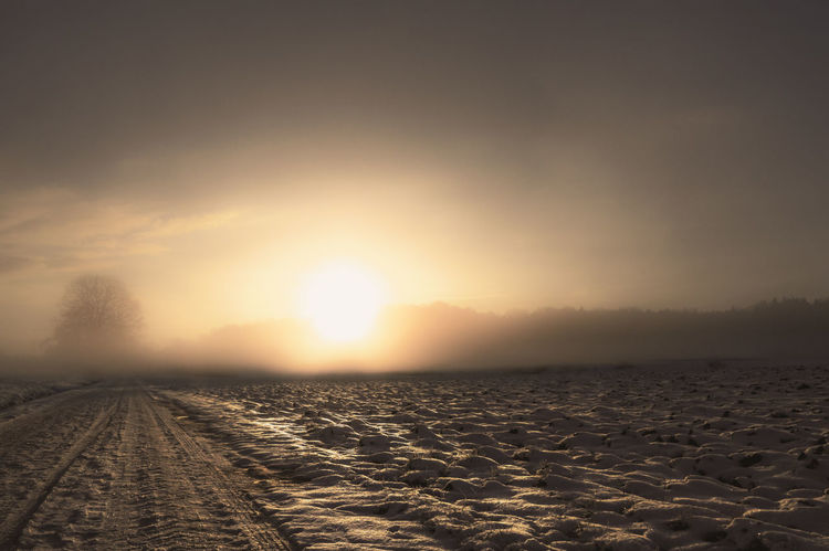 Winter sunrise with a countryside road in the middle of snowy fields, outside the german city Schwabisch Hall Snowy Road Copy Space Empty Road Environment Foggy Landscape Landscape Misty Landscape Nature No People Nobody Scenics - Nature Sky Snow Covered Snowy Field Sun Sunlight Sunrise Tire Track Tranquil Scene Tranquility A New Beginning
