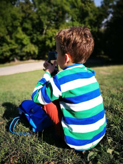 Rear view of boy sitting on field