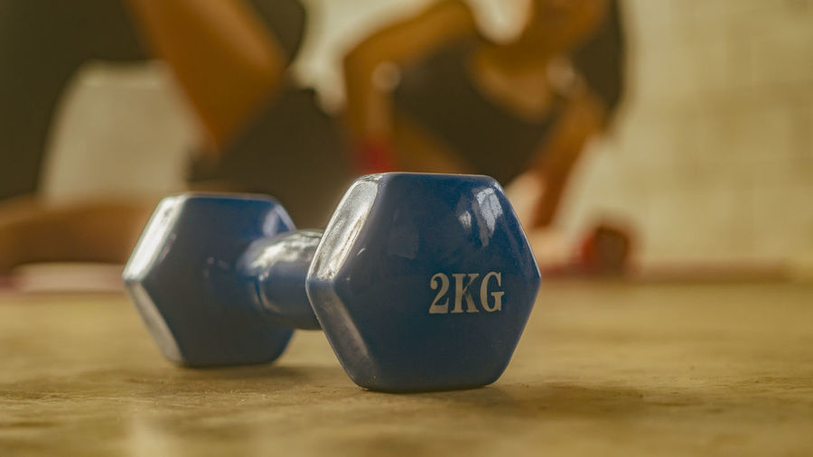 Dumbbell images placed in fitness with people exercising behind the concept of exercise for good health. Indoors  Sport Close-up One Person Exercising Sports Equipment Healthy Lifestyle Lifestyles Weights Selective Focus Adult Weight Training  Weight Leisure Activity Athlete Strength Focus On Foreground Dumbbell Sports Training